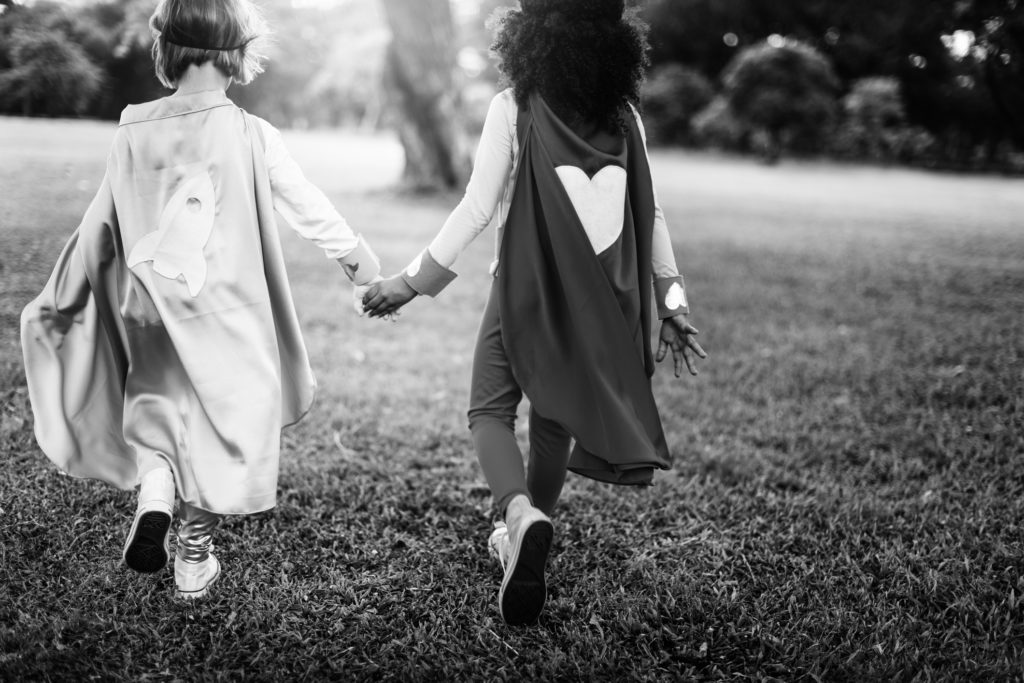 Children wearing capes, holding hands and running together